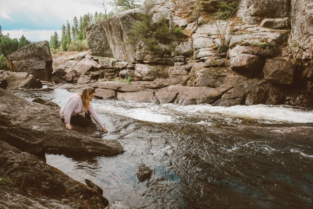 Taylor sits on a rock and dips her hands into the water at Tulabi Falls in Nopiming Provincial Park, Manitoba