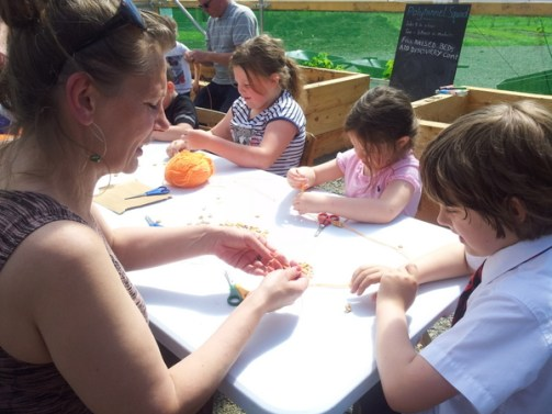 A groups of children around a table in polytunnel