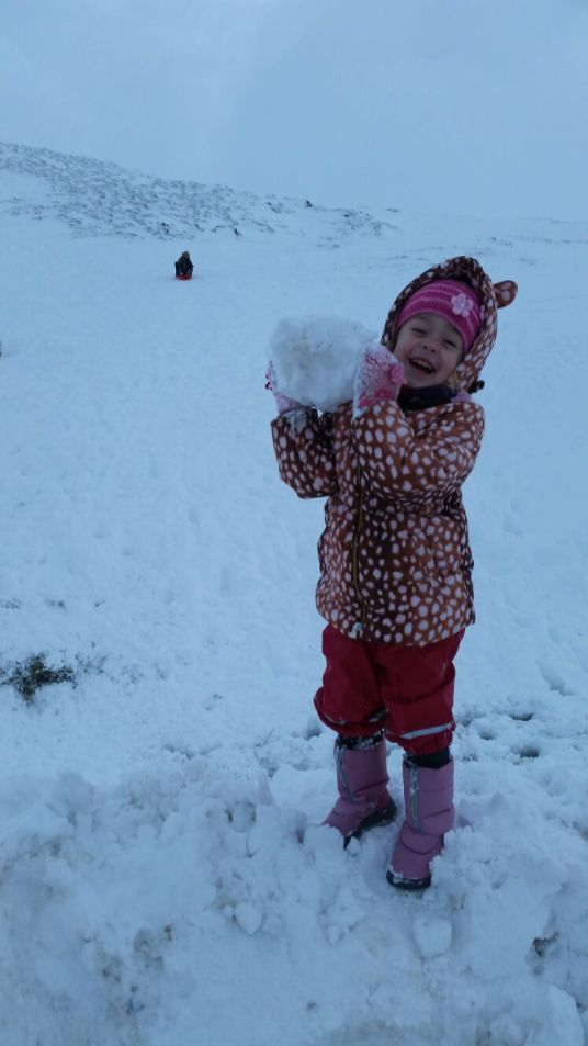 A photo of a girl playing with snow balls at Glenshee
