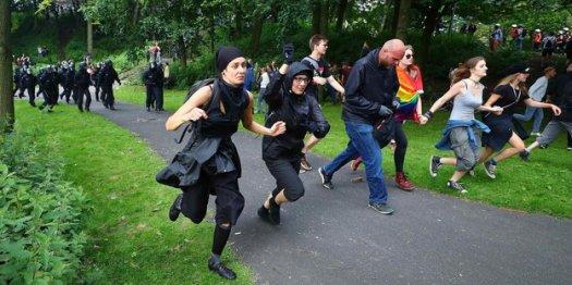 Demonstranten rennen in einer Reihe durch eine Grünanlage