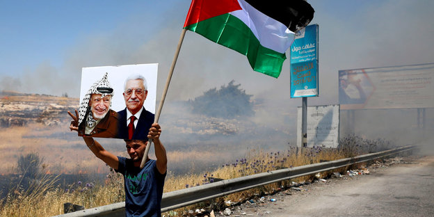 A man with a Palestinian flag holds up a photo of Arafat and Abbas