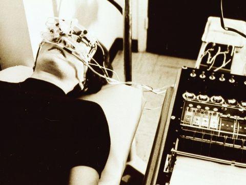 stock photo of woman lying on a gurney having an ERG test to diagnose retinitis pigmentosa.