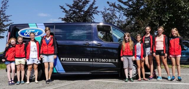 Die Mannschaft der D-Juniorinnen vor dem gestellten Bus, der Firma Pfizenmeier.