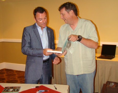 Peter Merry presenting Colin Cowie with a signed copy of TBWRE for Oprah