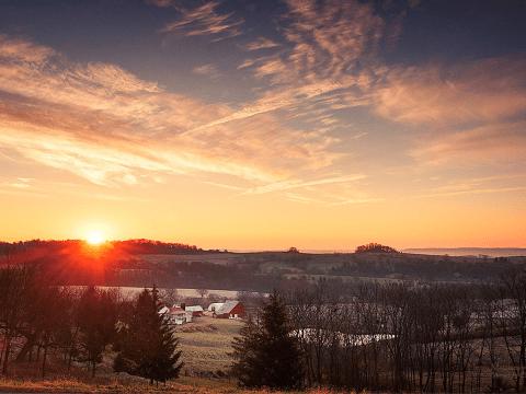 Setting sun over hillside and farm house
