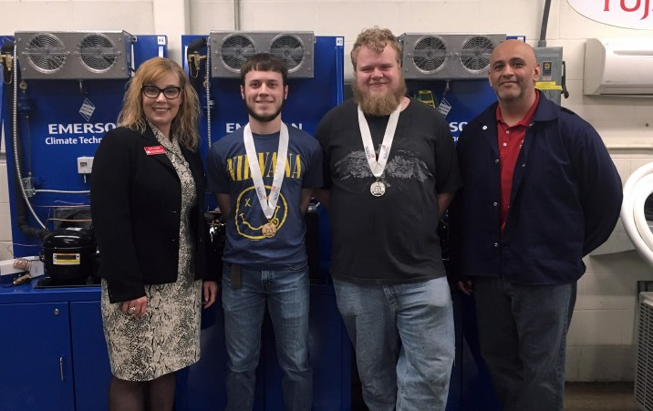 SCC President Lyn Cochran standing with winners Brennan Kearney, Brock Deschepper and HVAC instructor Zeke Gonzalez