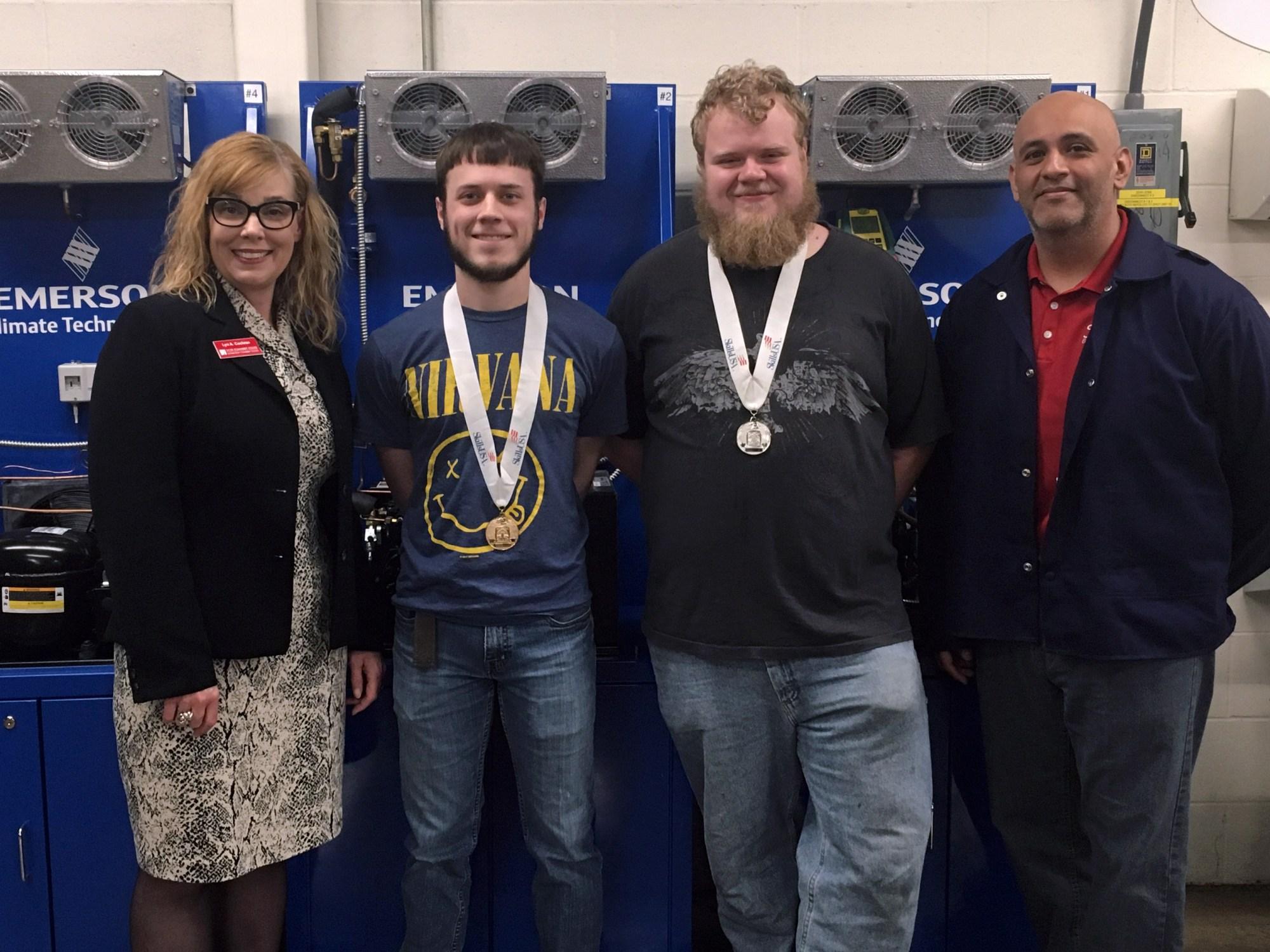 SCC President Lyn Cochran standing with winners Brennan Kearney, Brock Deschepper and HVAC instructor Zeke Gonzalez
