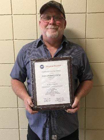 Ken Hunter standing with ASE Accreditation certificate