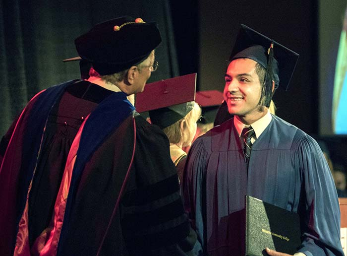 Male student accepting degree and shaking Chancellor Doucette's hand