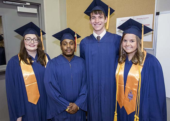 4 Graduates posing for photos in their blue caps and gowns