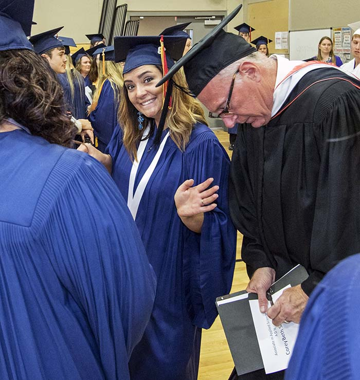 Students and Dean Serpliss standing in gym waiting for Commencement to start