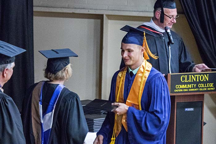 Male student with gold cords accepting his degree
