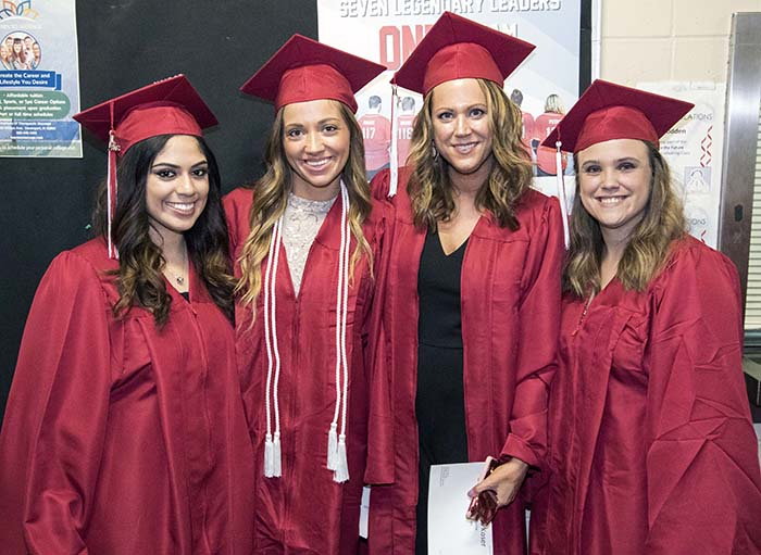 4 Graduates in red caps and gowns standing together