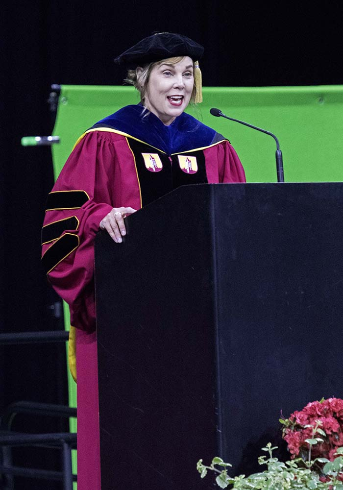 SCC President Lyn Cochran speaking at podium during commencement ceremony