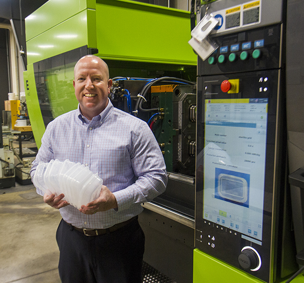 Jim Bratvett holding plastic sterilite containers next to the machinery that produces them