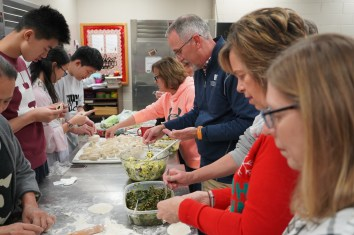 Multiple people making authentic chinese dumplings