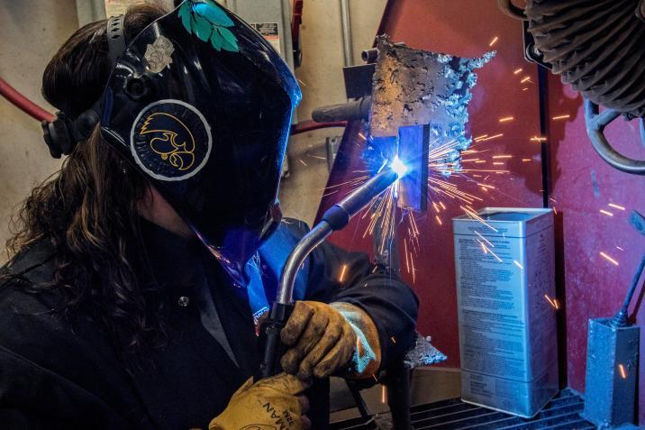Megan welding, blue sparks flying off metal