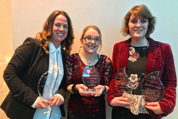 Winning graphic arts students holding awards