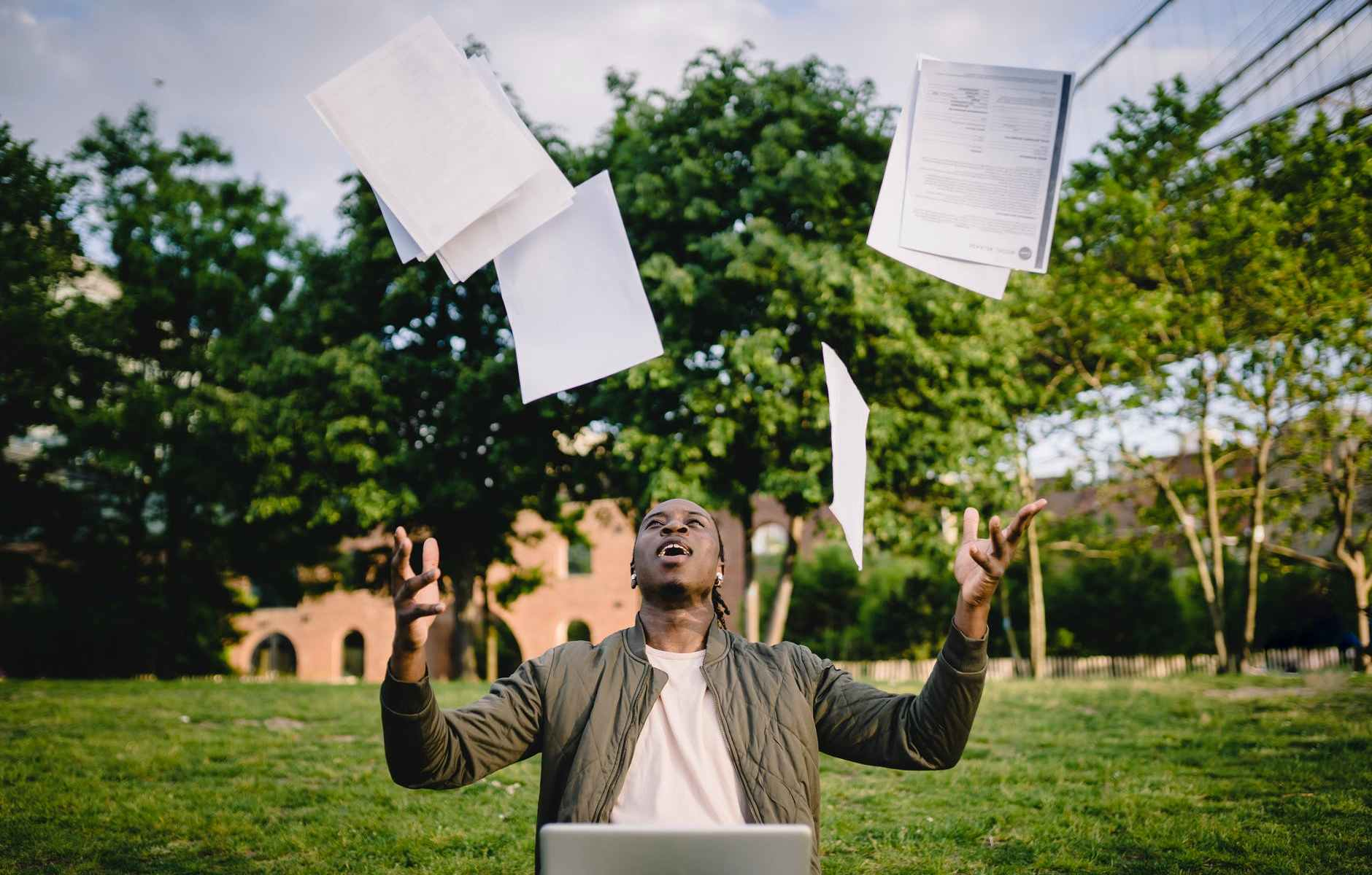 graduate with papers and laptop excited about getting job