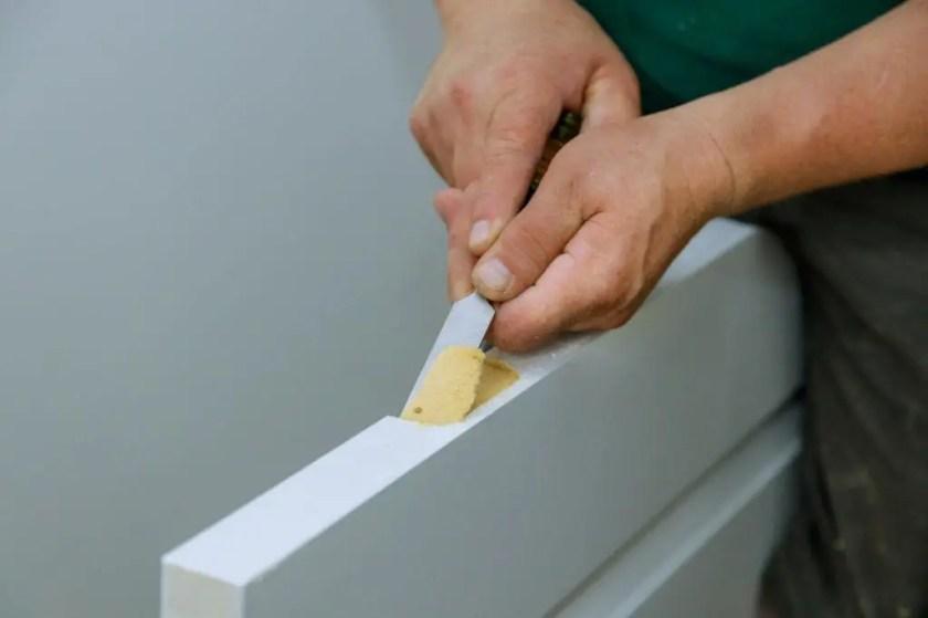 Carpenter cutting door hinges using a chisel