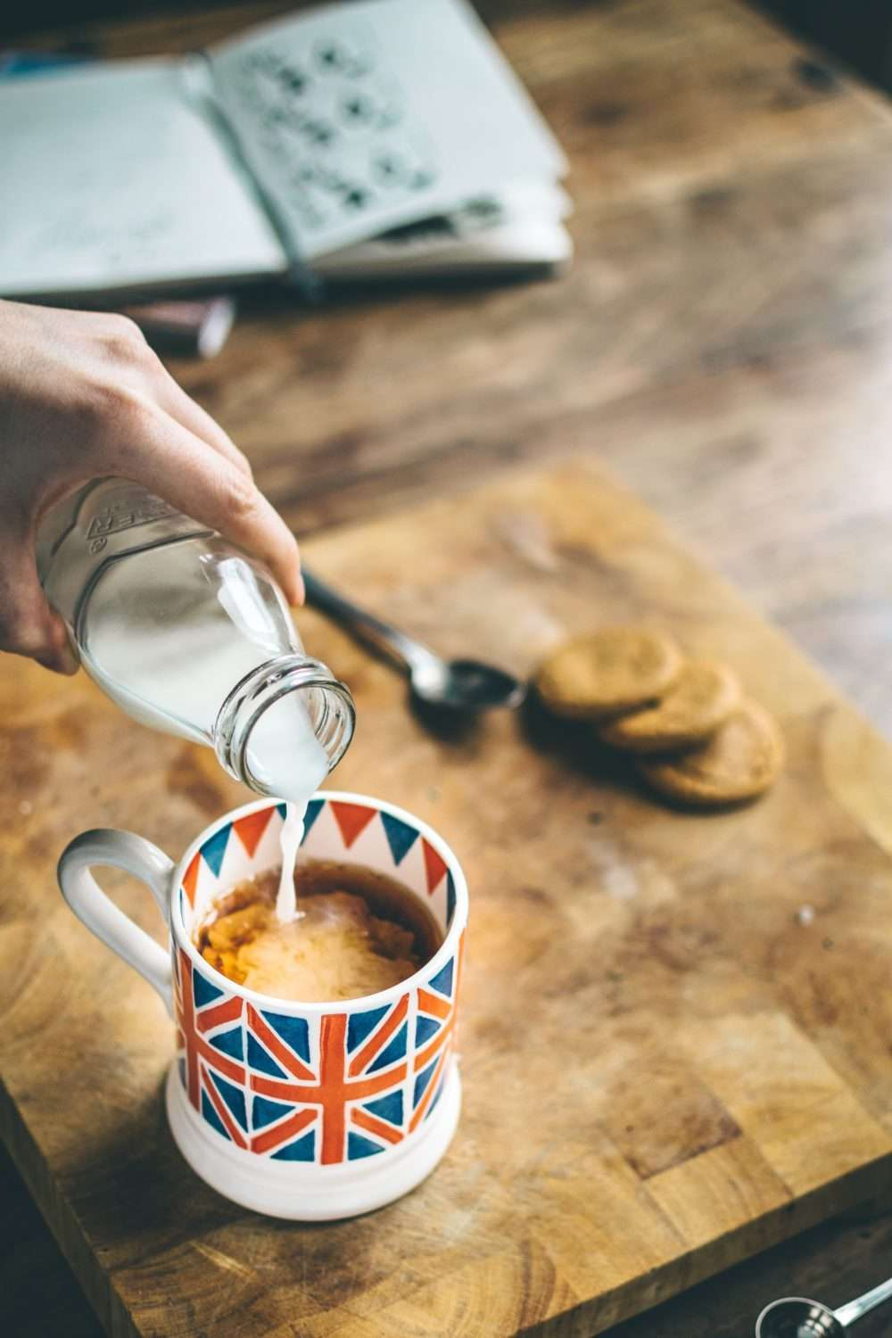 Tea And Cycling – A Perfect British Combination - Photo of pouring milk into a mug printed with the British flag that contains dark liquid