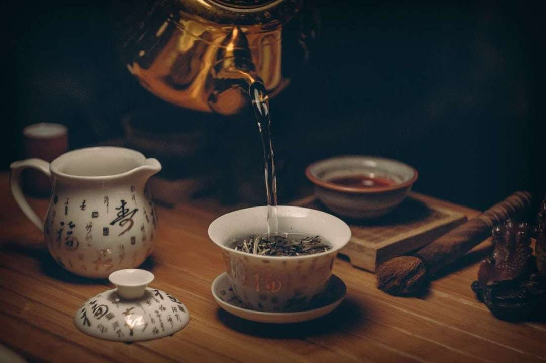 Photo of hot water being poured into a gaiwan of tea, with other tea tools nearby