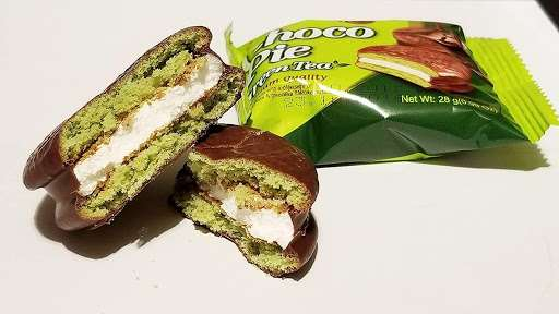 Photo of a Lotte Choco Pie Green Tea split in half to show the cream center, next to an individually-packaged treat.