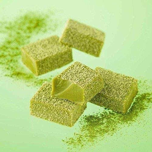 Photo of some Royce Nama Chocolate Maccha sweets spread out with matcha powder sprinkled around.
