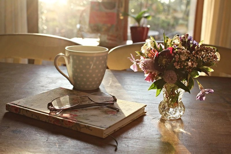 Spring tea in a mug on a table next to a vase of flowers and a book with glasses on it