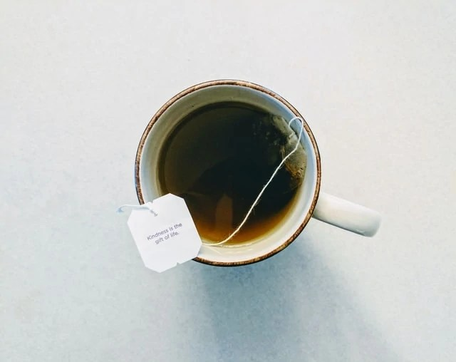 "Mug of tea with tea bag, the tag is balanced on the brim and says, ""Kindness is the gift of life"""