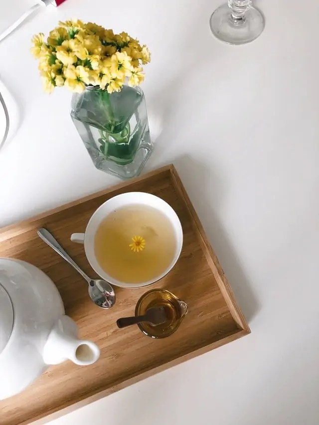 Teacup with tea and a flower floating in it, next to a teapot on a tray