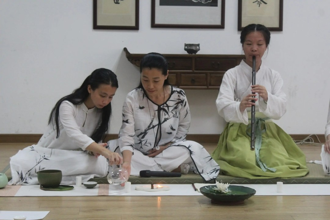 Three people sit on the floor during gongfu: One pouring, one assisting, one playing a flute