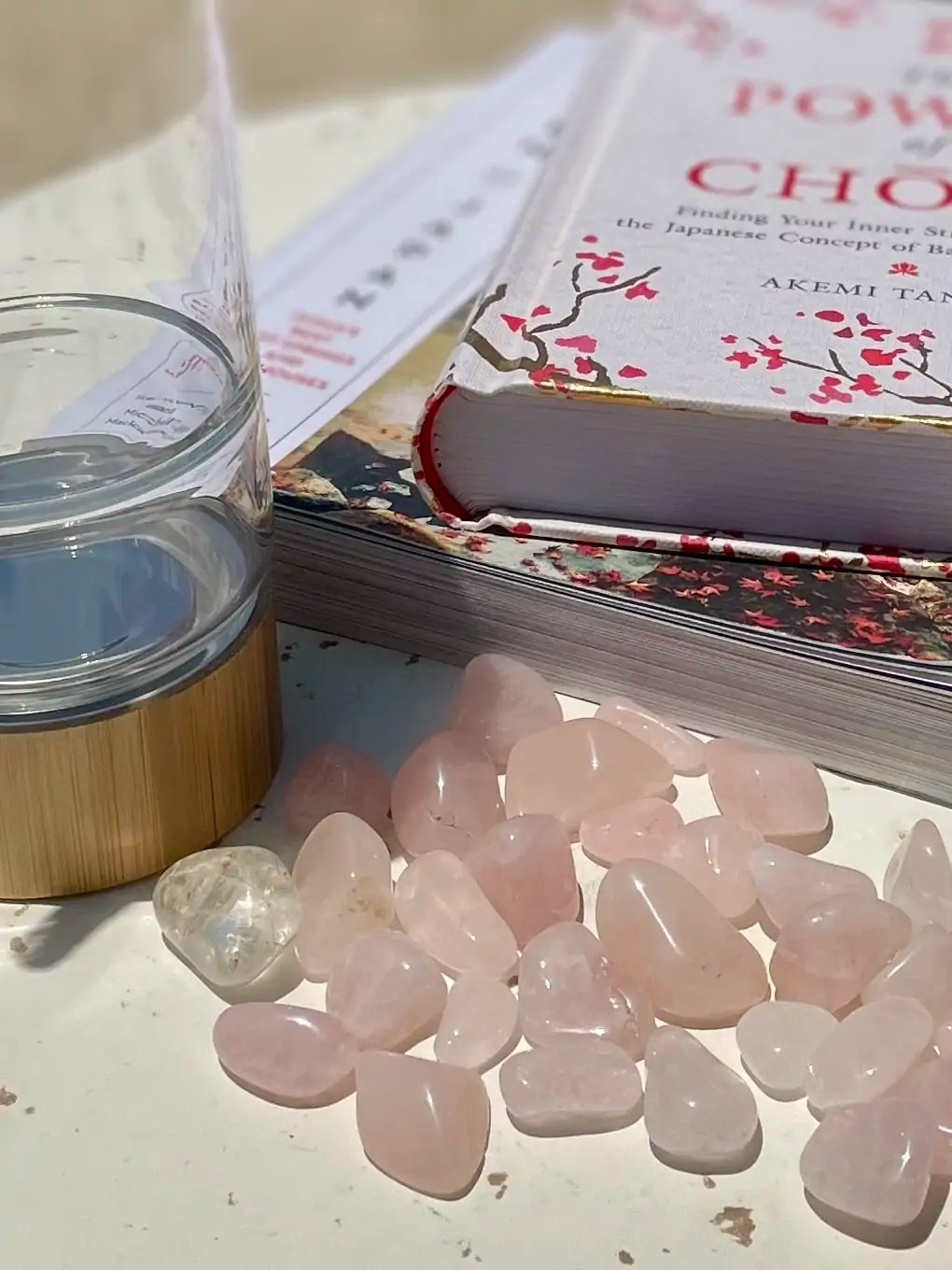 """Some tumbled rose quartz stones, next to a glass bottle, in front of a copy of """"The Hidden Messages in Water."""""""