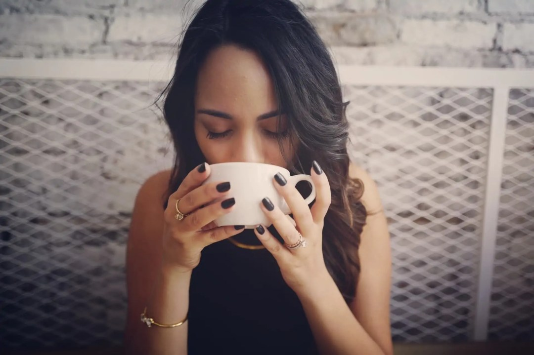 Woman holding a mug of tea up to her mouth, hiding her potentially stained teeth.