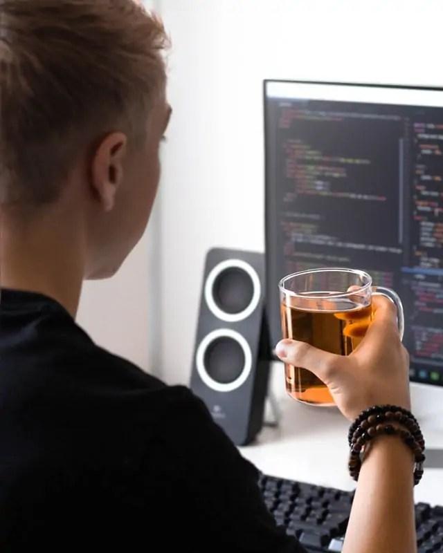Person holding mug of tea looking at computer screen