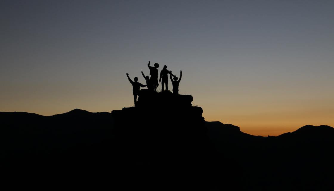 Group of 4 people silhouette on top of a hill with hands raised celebratory