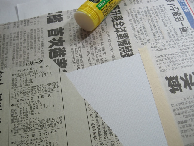 Adhere foreign newspaper with glue stick and coat with matte adhesive