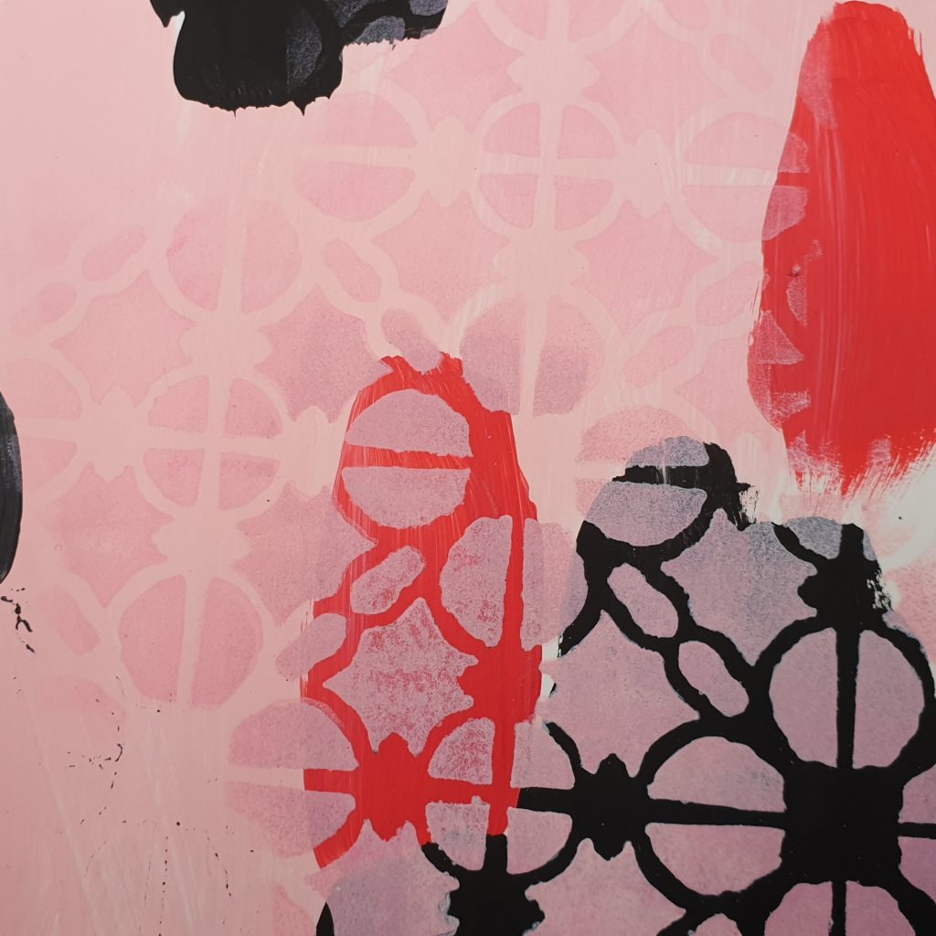 pink stenciling of TCW855 linked tiles over black and red