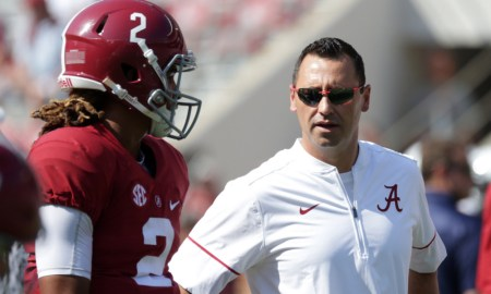 Steve Sarkisian speaking with Jalen Hurts on the field during 2016 season