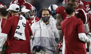 Nick Saban in a huddle during a stoppage