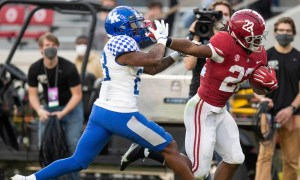 Najee Harris stiff arms a Kentucky defender and scores a touchdown