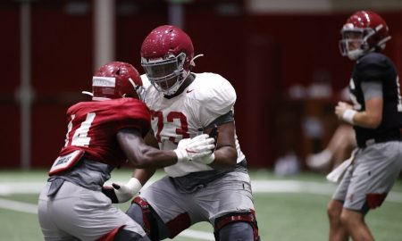 Evan Neal drops into a pass set at practice