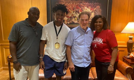 Nicholas Singleton poses for picture with his mom, dad and Nick Saban