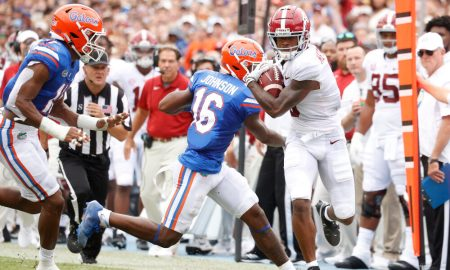 John Metchie runs up the sideline from two Florida defenders