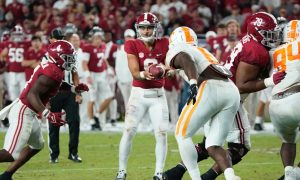 Bryce Young hands the ball off against Tennessee