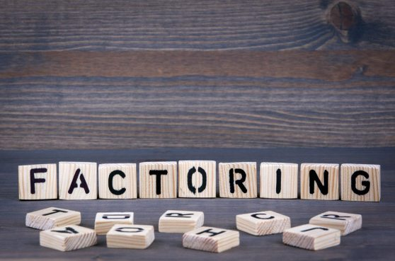 Factoring word written on wood block. Dark wood background with