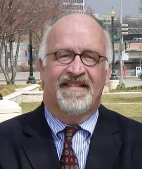 Older white white bald male wearing dark rimmed glasses. Wearing thin blue and white vertical stripped collared shirt, dark red tie with grayish circular pattern and dark jacket. Background is outdoor, somewhere in DC - tree, lamp-posts, street sign, grass