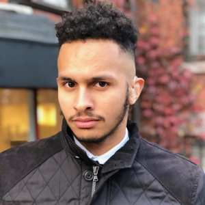 young male person of color with shaved fade, dark curly hair. lightly grown dark mustache and beard. Wearing dark zipped up jacket. Hearing aid visible in left ear.