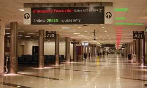 """Vacant airport terminal (gates A20, A21, A23). Sign displayed from ceiling """"Emergency Evacuation Gates A20 to A34) Follow GREEN Routes only"""" three green lights can be seen near the sign followed by a row of red lights."""