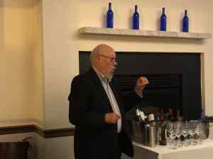 white bald male with salt & pepper goatee wearing dark glasses and dark jacket with light colored button down shirt standing next to a table of wine bottles and glasses.